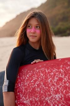 Dia de sol perfeito para surfar. surfista contemplativa em wetsuit, tem pele sã