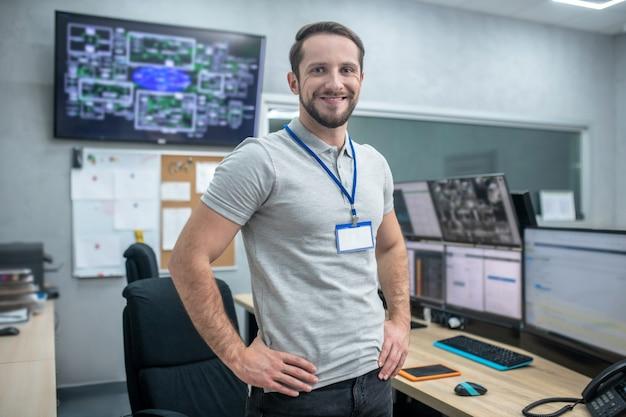 Dia de sorte. jovem alegre e atraente em camiseta e jeans em pé perto do local de trabalho com as mãos no cinto