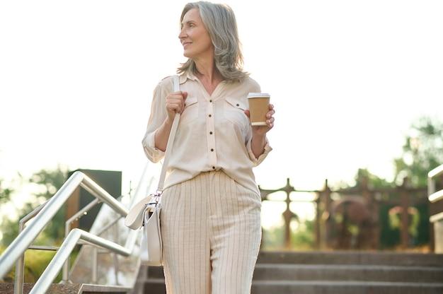 Dia de sorte. mulher bonita adulta elegante com café olhando para o lado na escada do parque num dia de verão