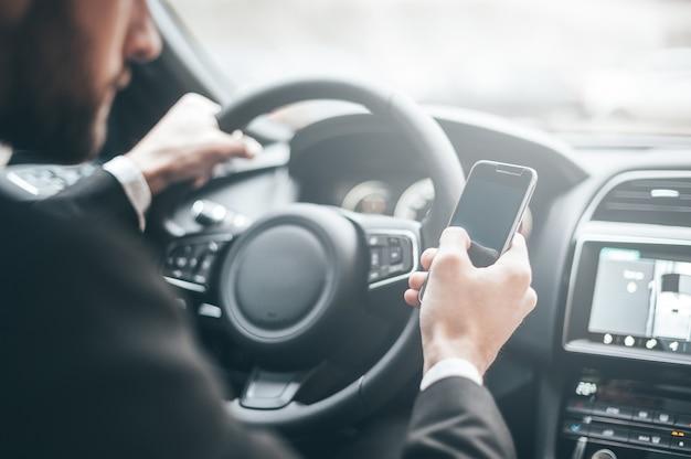 Dia de trabalho agitado. close-up do jovem empresário digitando algo no telefone inteligente enquanto dirige um carro