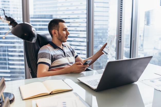 Dia de trabalho do analista financeiro, digitando no computador, analisando o trabalho com estatísticas sentado no local de trabalho contra a janela com vista da cidade
