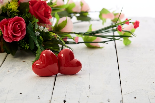 Dia de valentin romântico com coração vermelho e buquê de flores coloridas na mesa de madeira branca