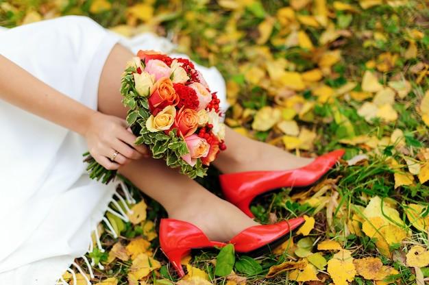 Dia do casamento. close-up dos pés da noiva em sapatos vermelhos, buquê de noiva colorido e folhas de outono na grama verde