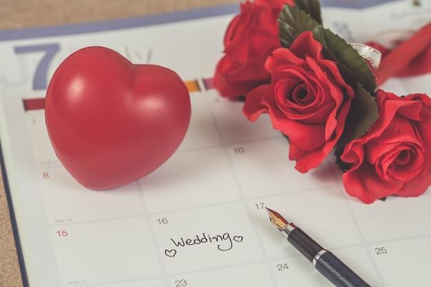 Dia do casamento do lembrete no planeamento do calendário e pena de fonte com tom da cor.