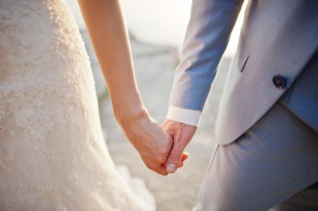 Dia do casamento. mãos nas mãos do casal recém-casado.