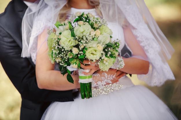 Dia do casamento. noiva com lindo buquê de noiva e noivo abraçando perto. casamento.