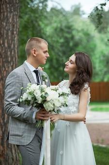 Dia do casamento, um casal apaixonado se abraçando e beijando no parque. homem abraça mulher bonita, noivado