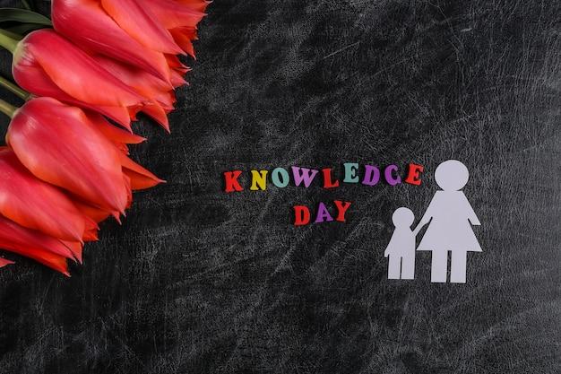 Dia do conhecimento. tulipas vermelhas com figuras de papel mãe e filho no quadro de giz. vista do topo. de volta à escola