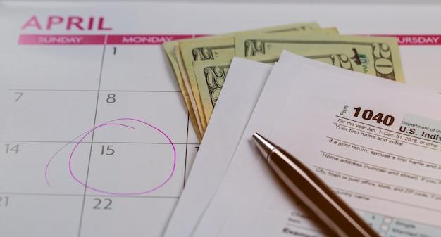 Dia do imposto, dólares e formulário formulário de imposto de renda 1040 mostrando o dia do imposto para o calendário de abril com palavras