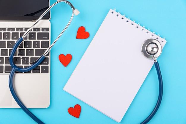 Dia do médico conceito, estetoscópio e peper nota com computador portátil