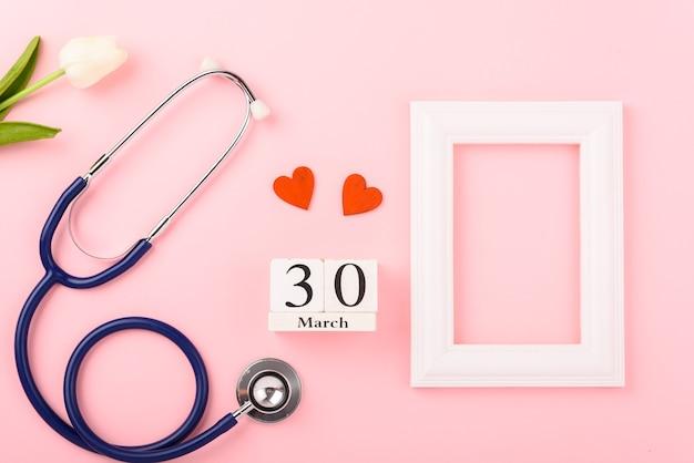 Dia do médico, estetoscópio de coração vermelho de equipamento médico e moldura
