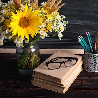 Dia do professor. placa de giz preto e flores silvestres frescas em vaso