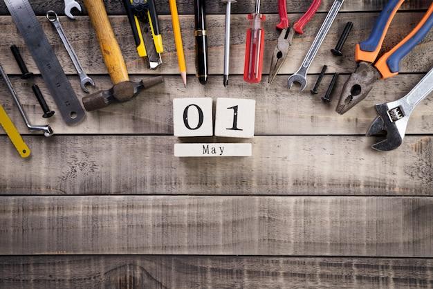 Dia do trabalho, calendário de bloco de madeira com muitas ferramentas úteis em fundo de madeira