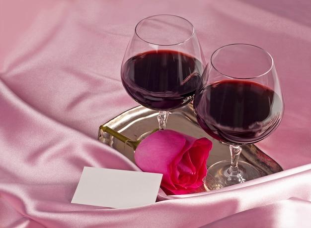 Dia dos namorados. caixa de presente, flores, copos com vinho no fundo de cor rosa