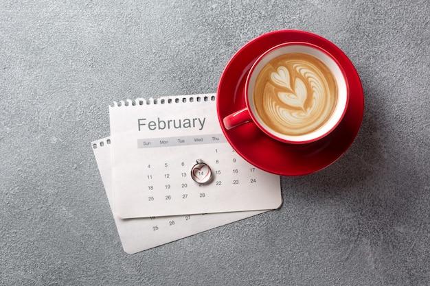 Dia dos namorados cartão. copo de café vermelho, anel e caixa de presente ao longo do calendário de fevereiro.