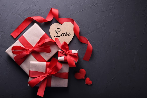 Dia dos namorados cartão de saudação amor símbolos, decoração vermelha com caixas de presentes em fundo de pedra. vista superior com cópia espaço e texto.