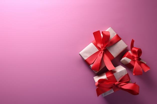 Dia dos namorados cartão de saudação amor símbolos, decoração vermelha com caixas de presentes em fundo rosa. vista superior com cópia espaço e texto.