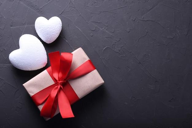 Dia dos namorados cartão de saudação amor símbolos, decoração vermelha com coração em fundo de pedra. vista superior com cópia espaço e texto.
