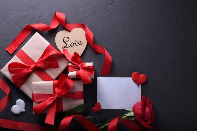 Dia dos namorados cartão de saudação amor símbolos, decoração vermelha com óculos coração rosas presentes em fundo de pedra. vista superior com cópia espaço e texto.