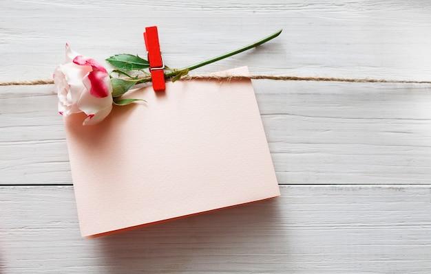 Dia dos namorados, cartão vazio e flor rosa em prendedor de roupa em pranchas de madeira rústicas brancas