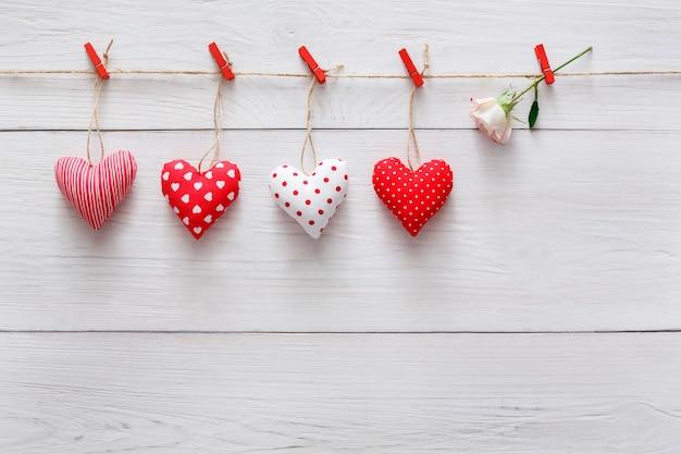 Dia dos namorados com almofada costurada diy corações feitos à mão borda de linha em prendedores de roupa vermelhos em pranchas de madeira branca rústica