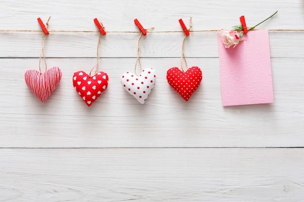 Dia dos namorados com borda de linha de corações de papel vermelho em prendedores de roupa e cartão de papel com flor rosa em pranchas de madeira rústica