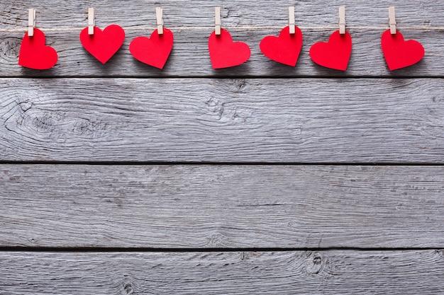 Dia dos namorados com borda de linha de corações de papel vermelho em prendedores de roupa em pranchas de madeira rústica