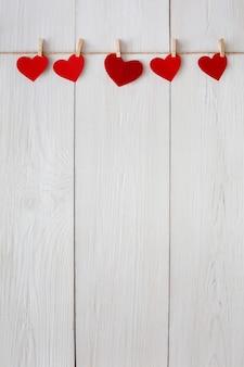 Dia dos namorados com borda de linha de corações de papel vermelho em prendedores de roupa em pranchas de madeira rústicas brancas