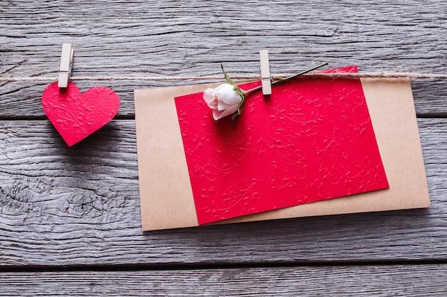 Dia dos namorados com coração de papel vermelho e cartão vazio em prendedores de roupa em pranchas de madeira rústicas