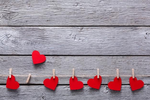 Dia dos namorados com corações de papel vermelho na borda de prendedores de roupa em pranchas de madeira rústica
