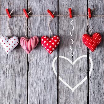 Dia dos namorados com corações de travesseiro costurados artesanalmente em prendedores de roupa vermelhos em pranchas de madeira rústicas azuis, verticais