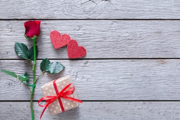 Dia dos namorados com flor rosa vermelha, corações de papel artesanais e caixa de presente em madeira rústica