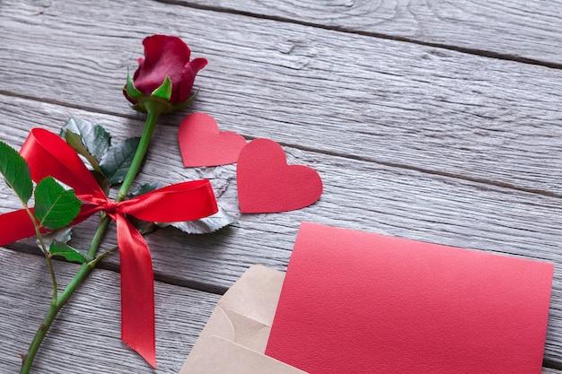 Dia dos namorados com flor rosa vermelha e corações de papel artesanal em madeira rústica na folha.