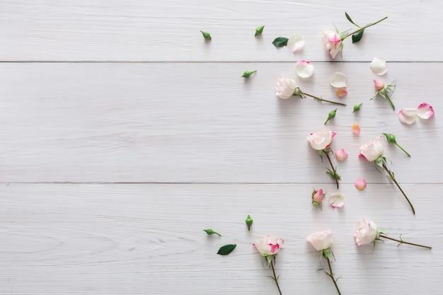Dia dos namorados com flores rosas espalhadas e pétalas com espaço de cópia em madeira rústica branca