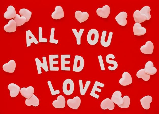 Dia dos namorados com fundo vermelho com corações rosa e a frase all you need is love forrado com letras de madeira brancas. dia das mães, cartão de 8 de março