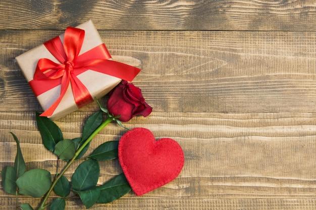 Dia dos namorados com presente de amor, rosas vermelhas, formas de perfume e coração. vista de cima. copyspace. postura plana.