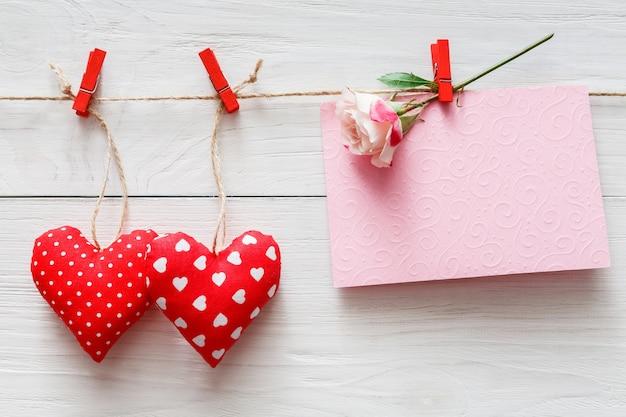 Dia dos namorados com travesseiro costurado, corações feitos à mão e cartão vazio em prendedores de roupa vermelhos em pranchas de madeira brancas rústicas