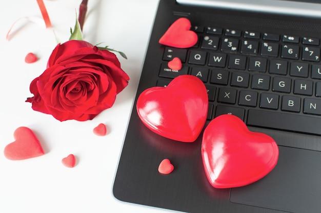 Dia dos namorados compras online. comunicação online, amor virtual. laptop, corações vermelhos, rosa vermelha.