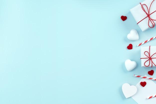 Dia dos namorados, conceito de design de arte do dia das mães para promoção - caixa de presente embrulhada vermelha, branca, isolada no fundo de cor azul claro pastel, leiga plana, vista superior.