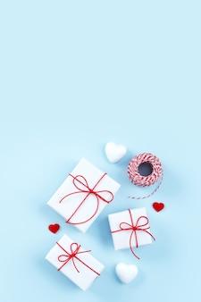 Dia dos namorados, conceito de design de presente feito à mão de dia das mães - caixa de presente embrulhada isolada no fundo de cor azul claro pastel, leiga plana, vista superior.