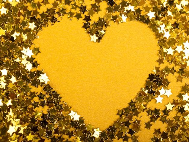 Dia dos namorados coração de estrelas douradas sobre um fundo amarelo.