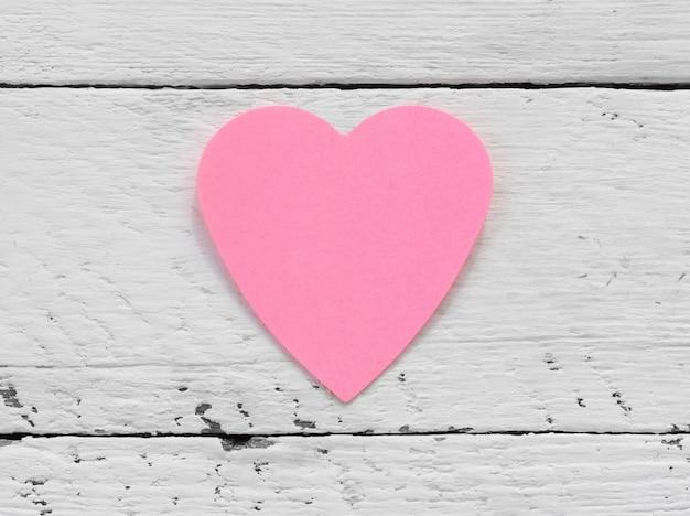 Dia dos namorados - coração rosa de papel contra uma superfície pintada de branca.