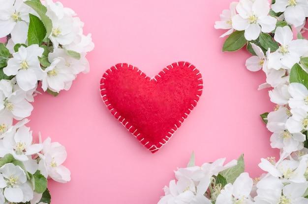 Dia dos namorados, coração vermelho com uma moldura de flores e folhas em um fundo rosa