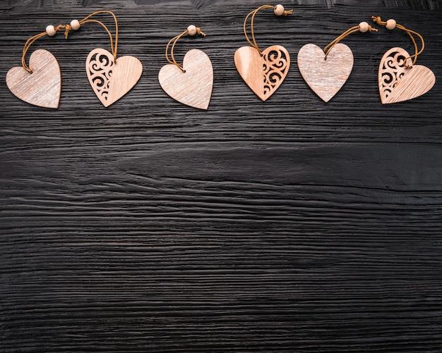 Dia dos namorados. corações de madeira em uma madeira preta