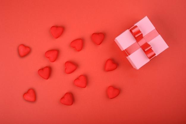 Dia dos namorados. corações vermelhos com uma caixa de presente em um fundo vermelho