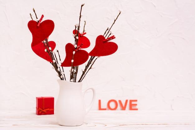 Dia dos namorados. corações vermelhos feitos de feltro em galhos de salgueiro em um jarro branco em cima da mesa, um presente e a palavra