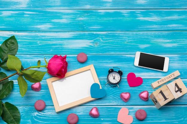 Dia dos namorados criativo composição romântica plana leiga vista superior amor feriado celebração coração vermelho data do calendário fundo de madeira azul