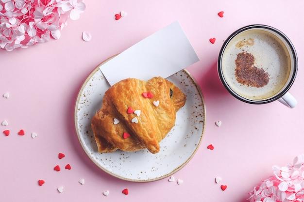 Dia dos namorados deitado com duas xícaras de café, croissant no prato rosa