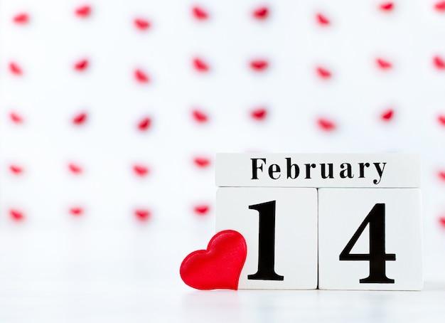 Dia dos namorados do conceito. calendário de madeira show de 14 de fevereiro com coração vermelho