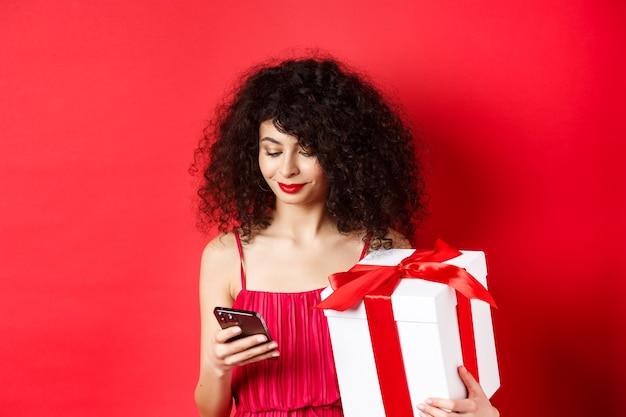 Dia dos namorados e compras. linda mulher caucasiana com vestido vermelho, segurando a caixa de presente do amante e usando o telefone celular, lendo a mensagem no smartphone, plano de fundo do estúdio.